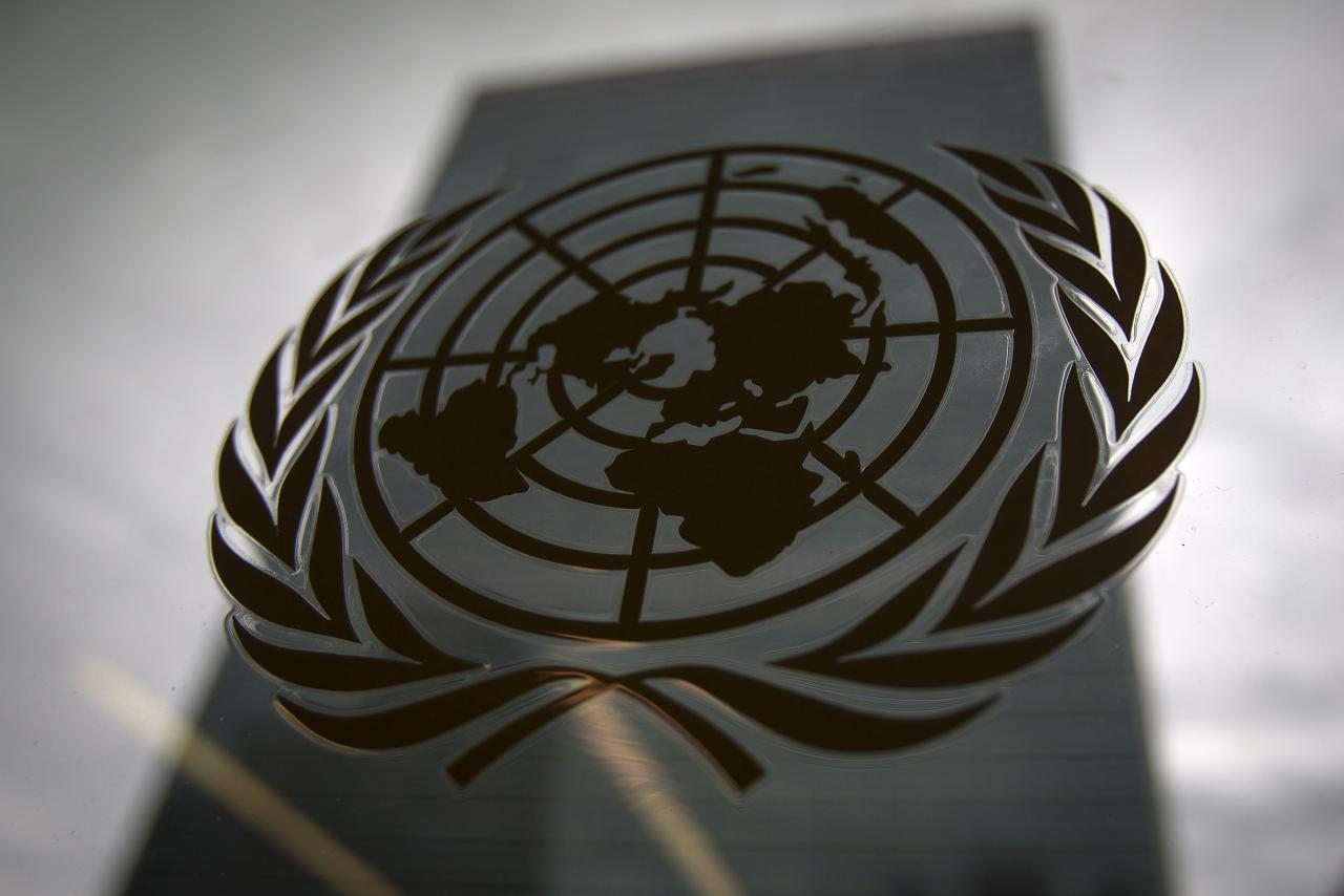 The United Nations headquarters building is pictured though a window with the UN logo in the foreground in the Manhattan borough of New York August 15, 2014.    REUTERS/Carlo Allegri/Files