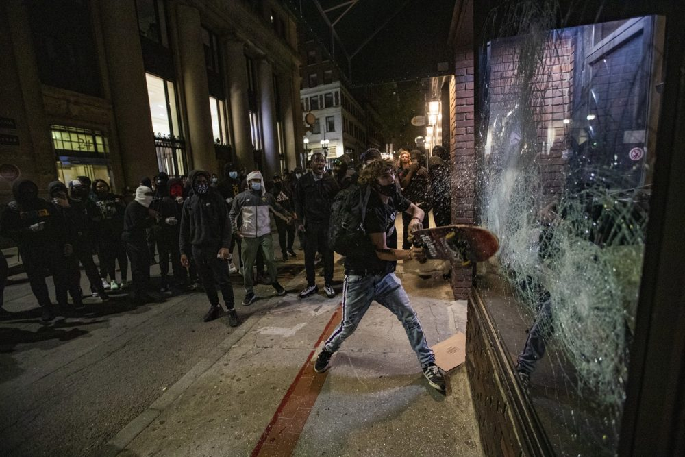 Looters smashing a window of a store front on School street after the Black Lives Matter rally at the Massachusetts State House. (Jesse Costa/WBUR)