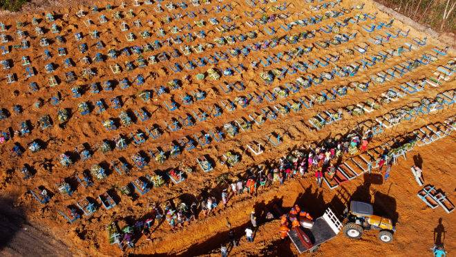 Aerial view of cemetery workers unloading a coffin from a truck at an area where new graves have been dug at the Parque Taruma cemetery, during the COVID-19 coronavirus pandemic in Manaus, Amazonas state, Brazil, on April 21, 2020. - Graves are being dug at a new area of the cemetery for suspected and confirmed victims of the COVID-19 coronavirus pandemic. (Photo by MICHAEL DANTAS / AFP)
