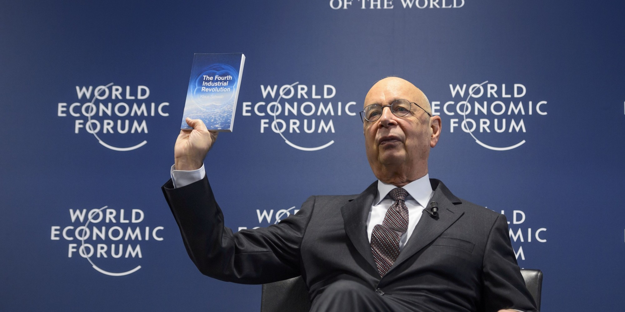 World Economic Forum (WEF) founder and executive chairman Klaus Schwab shows a book he wrote during a news conference on the programme of the Davos World Economic Forum WEF annual meeting at the Forum's headquarters in Cologny, near Geneva, on January 13, 2016. This year's edition of the forum gathering of top politicians and business leaders in the plush Swiss ski resort of Davos is scheduled to take place from January 20 to 23.  / AFP / FABRICE COFFRINI        (Photo credit should read FABRICE COFFRINI/AFP/Getty Images)