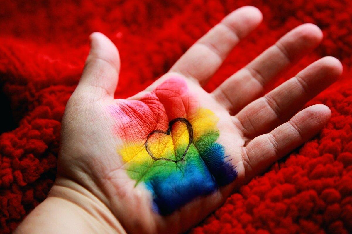 Mão de uma criança pintada com bandeira do orgulho LGBT e um coração no cento